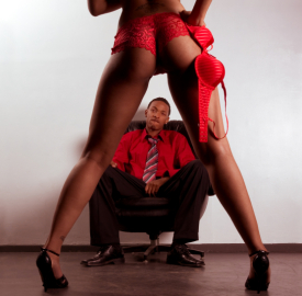 Striper woman in red dancing for young black man