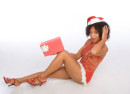 Dark skinned mid-aged female in sexy Christmas costume sitting on floor and holding gift box wrapped in red paper with white bow