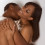 Loving ethnic black African-American young affectionate nude heterosexual couple in affectionate sensual kiss.
