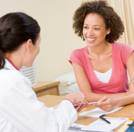 Woman in doctor's office discussing results smiling