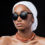 Beautiful African woman wearing a headscarf and sunglasses while standing against black background